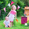 Little kids playing with toy kitchen in the garden — Stock Photo #51020579