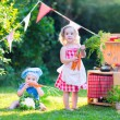 Little kids playing with toy kitchen in the garden — Stock Photo #51342577