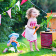 Little kids playing with toy kitchen in the garden — Stock Photo #51342681