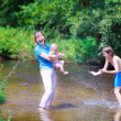 Family enjoying hot day on a river — Stock Photo