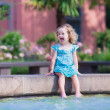 Little girl refreshing in a fountain — Stock Photo #51343125