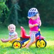 Two kids on a bike in the garden — Stock Photo