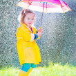 Funny toddler with umbrella playing in the rain — Stock Photo #51344445