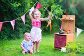 Little kids playing with toy kitchen in the garden — Стоковое фото