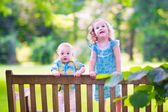 Brother and sister on a park bench — Stock Photo
