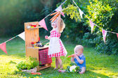 Little kids playing with toy kitchen in the garden — Stock Photo