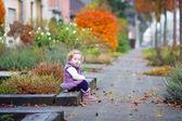Little girl in a autumn city street — Stock Photo