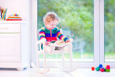 Little girl with a book in a rocking chair — Stock Photo