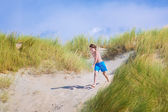 Happy child jumping in the dunes — Stock Photo