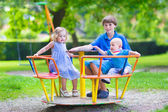 Three kids on a swing — Stock Photo