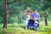 Active parent hiking with two kids in a stroller — Stock Photo