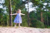 Little girl running on sand dunes — Stock Photo