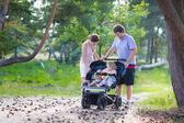 Young family hiking with two kids in a stroller — Stock Photo