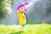 Funny toddler with umbrella playing in the rain — Stock Photo