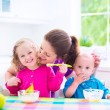 Mother and kids having breakfast — Stock Photo #51615547
