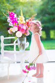 Little girl smelling flowers at home — Stock Photo