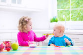 Two children eating yoghurt — Stock Photo
