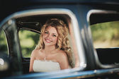 Bride sitting in car and smile — Stock Photo