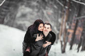 Loving couple having fun in a snowy forest — Stockfoto