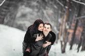Loving couple having fun in a snowy forest — Foto de Stock