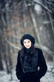 Beautiful girl standing in a snowy forest — Foto Stock