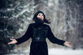 Beautiful girl standing in a snowy forest — Foto de Stock