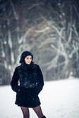 Beautiful girl standing in a snowy forest — Стоковое фото
