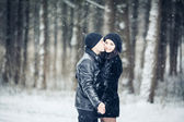 Couple in love kissing in the winter forest — Stockfoto