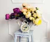 Clock, chair and bouquet of flowers — Stock Photo