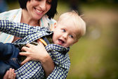 Mother playing with her son and lifting him rejoicing — Stock Photo