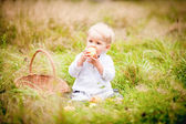 Little boy with a basket and eats it with fruit — ストック写真