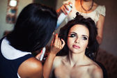 Wedding. Young beautiful girl applying make-up by make-up artist — Photo