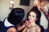 Wedding. Young beautiful girl applying make-up by make-up artist — Stok fotoğraf