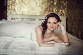 Wedding. Beautiful woman lying on the bed in her bedroom — Stockfoto