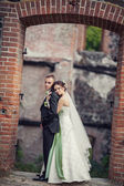 Wedding. bride and groom embracing against the backdrop of an old building — Photo