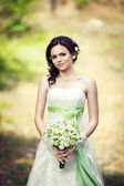 Beautiful bride outdoors in a forestwith with bouquet of beautiful roses — Stock Photo