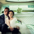 Wedding. Bride and groom kissing in limousine on wedding-day. — Stock Photo #43438639