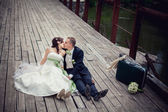 Wedding. Beautiful newly married couple kissing on a bridge — Stock Photo