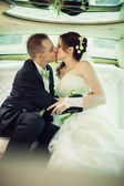 Wedding. Bride and groom kissing in limousine on wedding-day. — Stock Photo