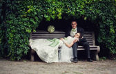 Wedding, the couple hid under the arch of leaves on the bench. nature — Stock Photo