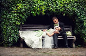 Wedding, the couple hid under the arch of leaves on the bench. n — Stock Photo
