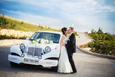 Happy bride and groom near retro car — Stock Photo