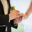 Groom's hand putting a wedding ring on the bride's finger — 图库照片