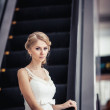 Blonde bride standing near the escalator — Stock Photo