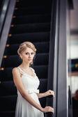 Blonde bride standing near the escalator — Stock Photo