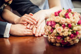 Hands with wedding rings amd bouquet — Stock Photo