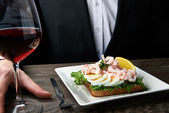 Man eating delicious shrimp salad sandwich on a plate — Stock Photo