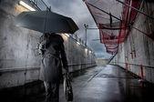 Businessman holding black umbrella on rainy day — Stock Photo