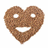 Heart with smiling face from buckwheat — Stock Photo