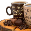 Two cups of coffee, chocolate hearts and coffee beans on the stump isolated — Stock Photo #45178629